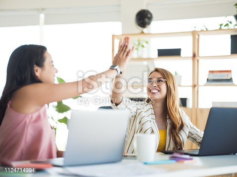 1031394114 istock photo Young  woman celebrating with high fives in the office 1124714994