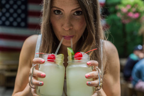 Young woman celebrating with two frozen drinks Young lady in-front of American flag enjoying two frozen drinks margaritas with red cherries day 4 stock pictures, royalty-free photos & images