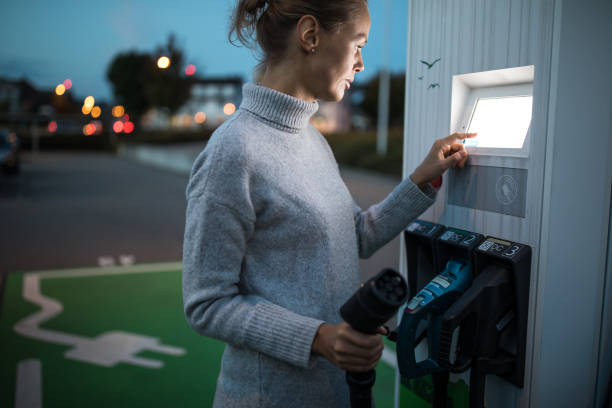 young woman charging an electric vehicle - macchina ibrida foto e immagini stock