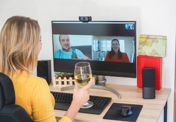 young woman chatting with friends drinking wine and laughing together - alternative party during home isolation quarantine - focus on glass hand - remote work imagens e fotografias de stock