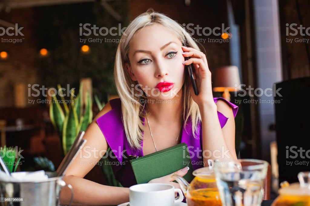 Young woman chatting with smartphone in restaurant stock photo