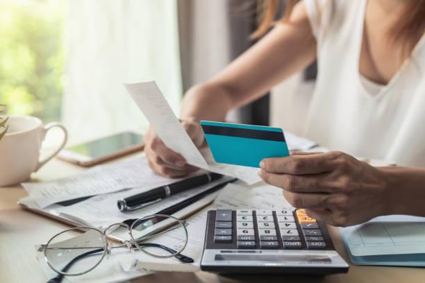 mujer joven comprobación de facturas, impuestos, saldo de la cuenta de banco y el cálculo de gastos de tarjeta de crédito en casa - deuda fotografías e imágenes de stock