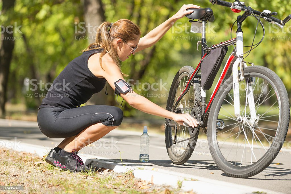 Young woman checking her bicycle in park royalty-free stock photo