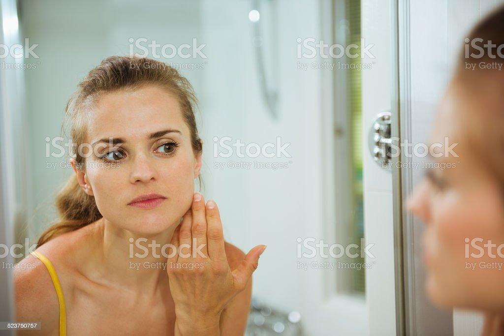 Junge Frau, die Ihr Gesicht im Spiegel – Foto