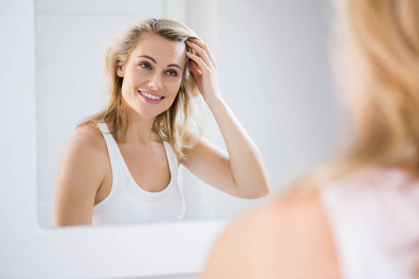 Young woman checking her hair in bathroom mirror stock photo
