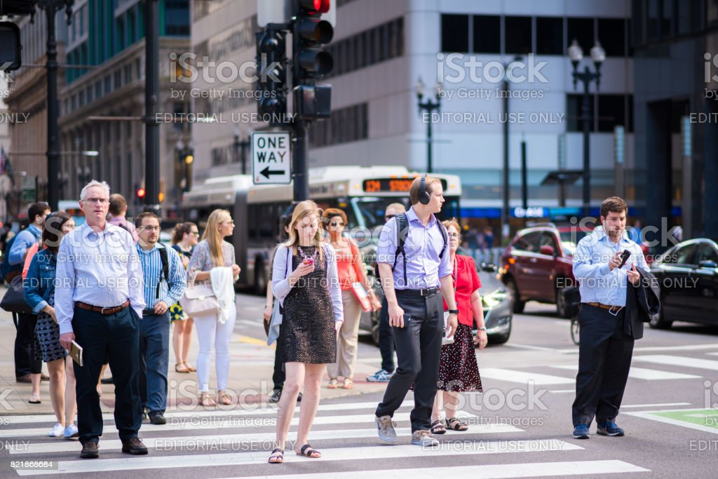 Young woman checking her phone at an intersection stock photo
