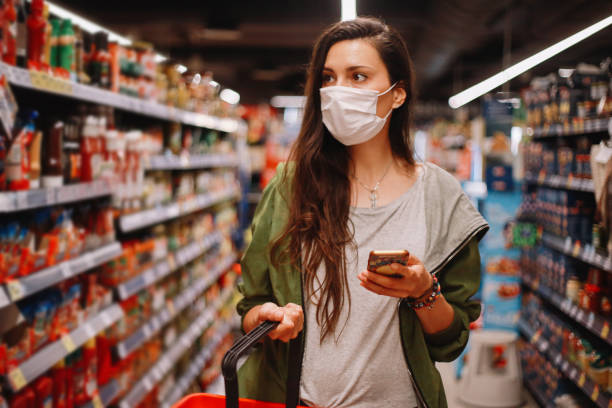 young woman checking her shopping list on the smartphone stock photo