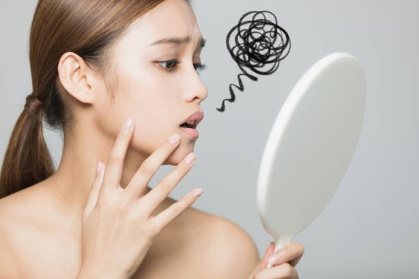 Young woman checking her skin. Skin care concept. stock photo