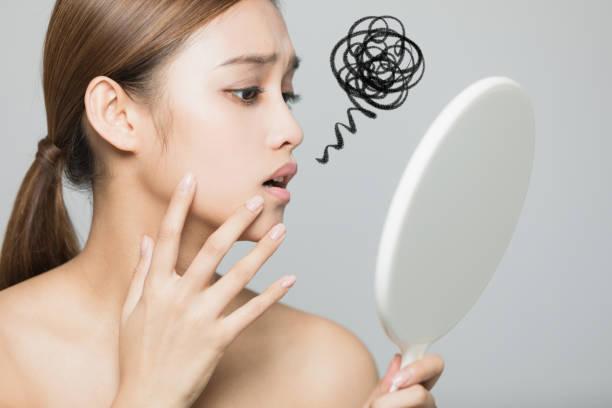 若い女性が彼女の肌をチェックします。肌ケアのコンセプトです。 - 肌荒れ ストックフォトと画像