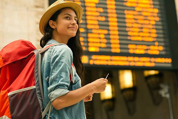 young woman checking her train in time board - airport terminal stock photos and pictures