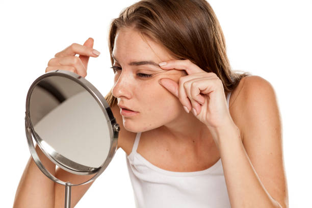 Young woman checking her wrinkles on her eyes stock photo