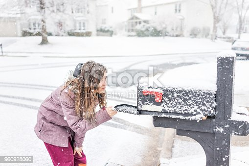 istock Young woman checking mail in neighborhood road with snow covered ground during blizzard white storm, snowflakes falling in Virginia suburbs, single family homes in mailbox box 960928060