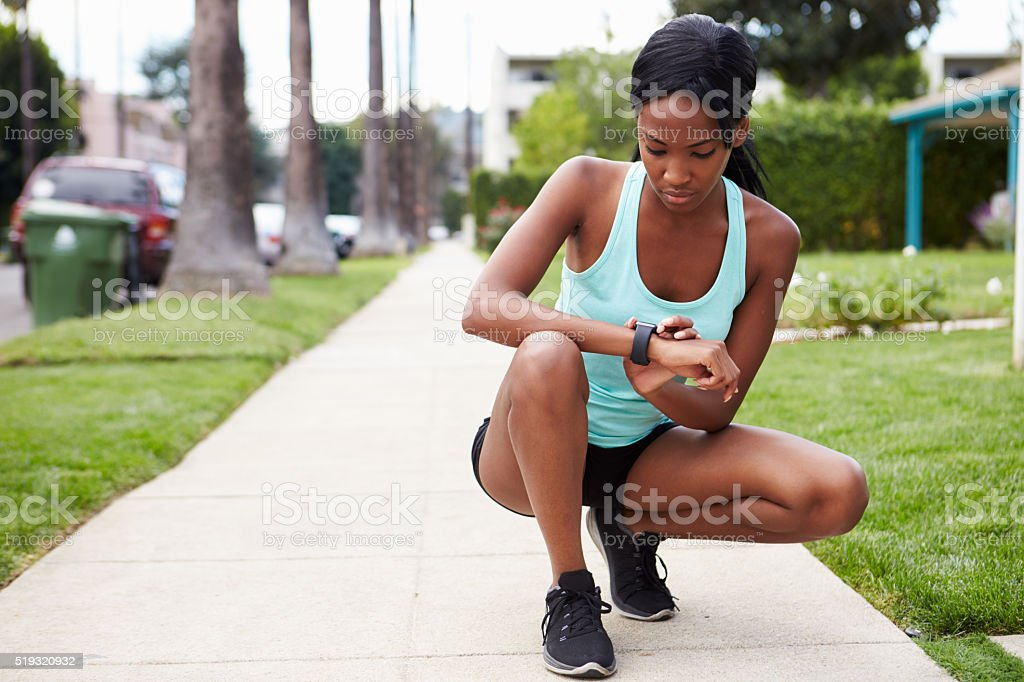 Young woman checking smart watch in the street before stock photo