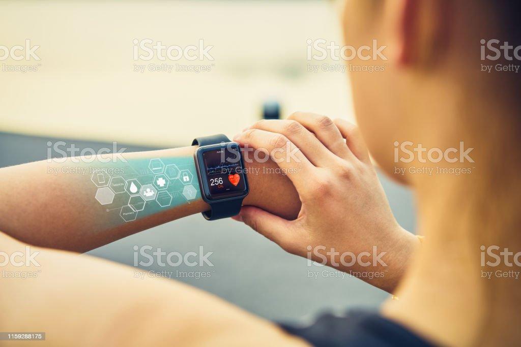 Junge Frau überprüfen die Sportuhr mit Bildschirm Gesundheits-Symbol, Messung der Herzfrequenz und Leistung nach dem Laufen. - Lizenzfrei Anfang Stock-Foto