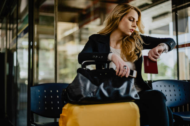 Young woman checking the time and waiting at the airport stock photo