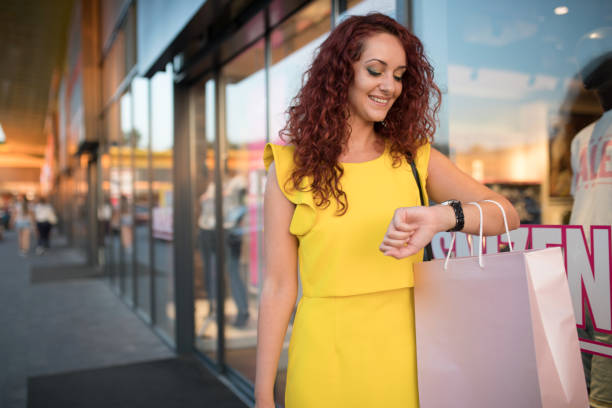 Young woman checking the time in shopping stock photo