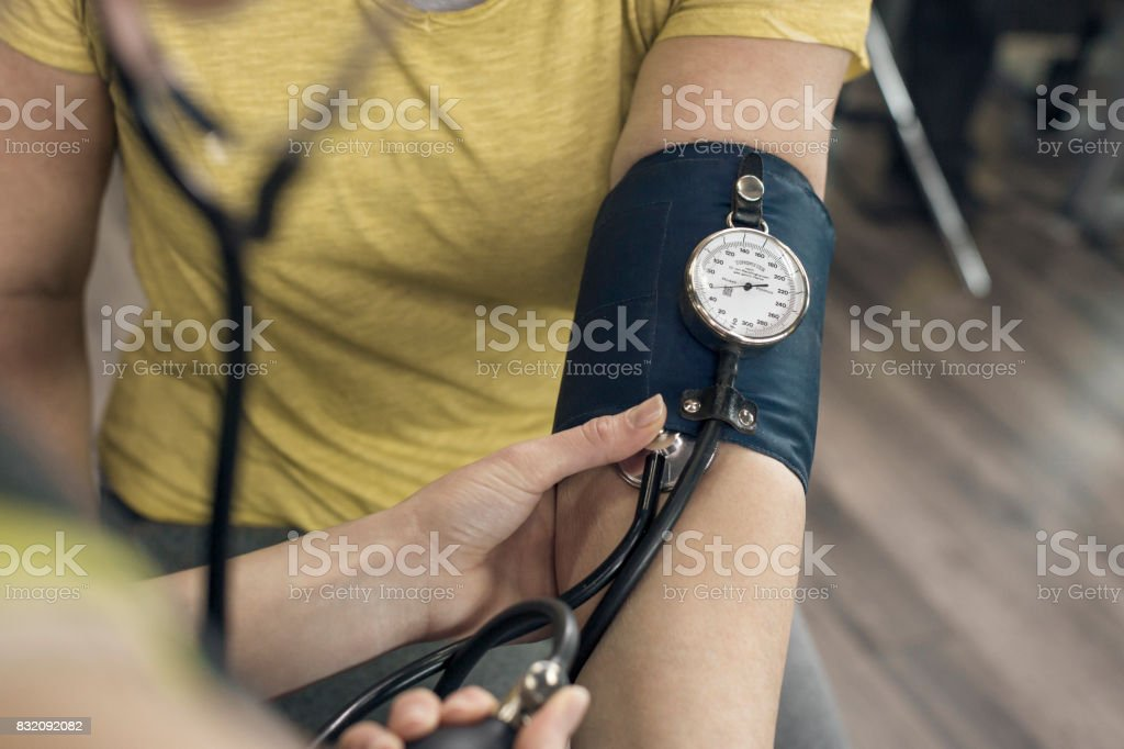 A young woman checks blood pressure In The Gym stock photo