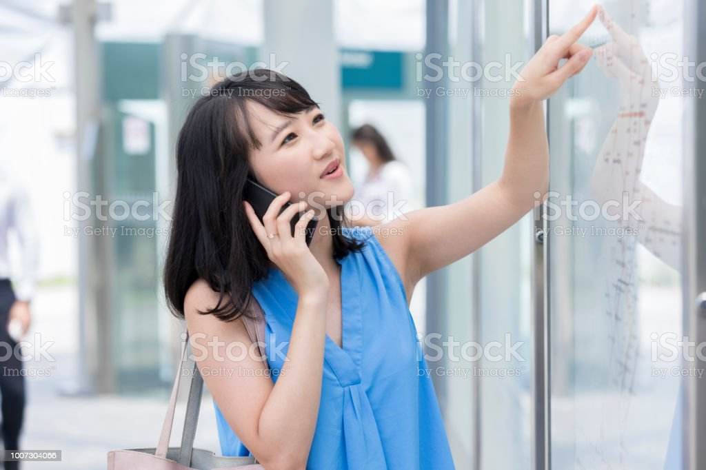 Young woman checks map at train station stock photo