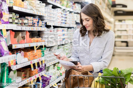 A serious young woman pauses in the dairy aisle at the grocery store to read the label on a yogurt container.  She is holding a shopping list and smart phone.