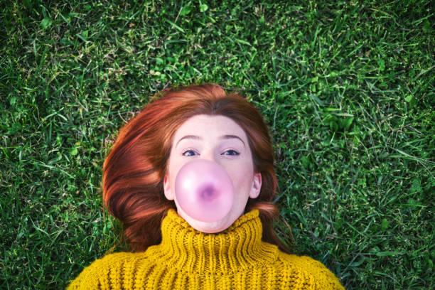 Junge Frau Kaugummi und machen großen Ballon – Foto