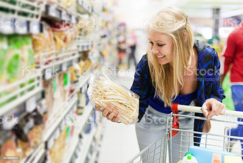 Young woman chooses a packet of pasta in a supermarket stock photo