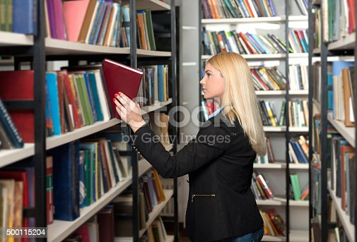 istock young woman choosing a book in the library 500115204