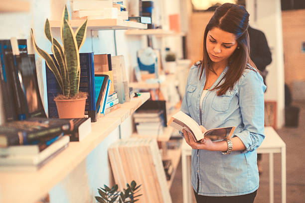 young woman choosing a book stock photo