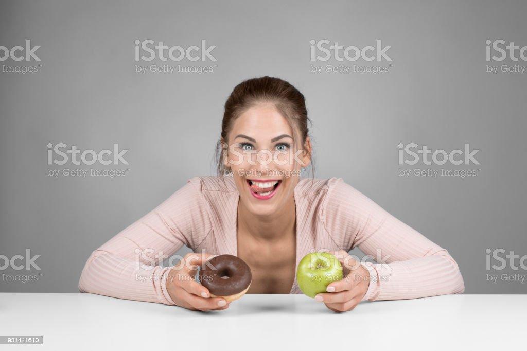 Junge Frau die Wahl zwischen Donut und Apple – Foto