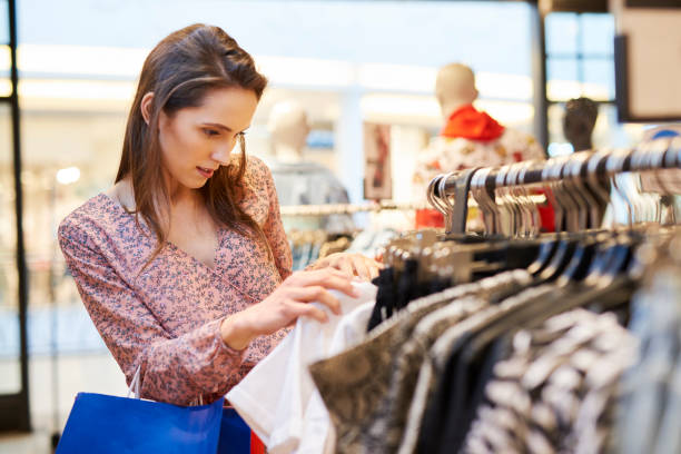 Young woman choosing blouse in the clothes shop stock photo