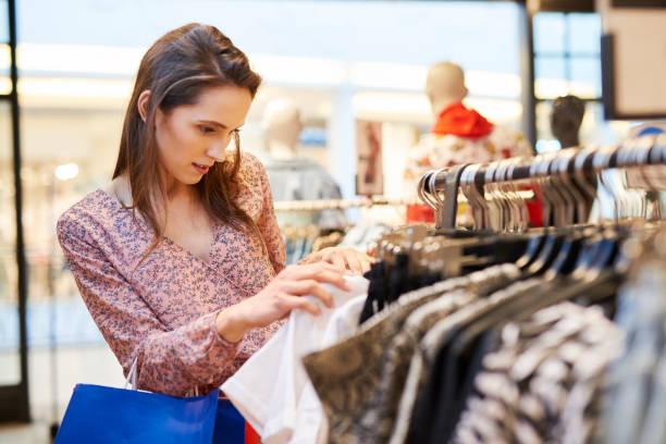 jonge vrouw kiezen blouse in de kleding winkel - kledingwinkel stockfoto's en -beelden