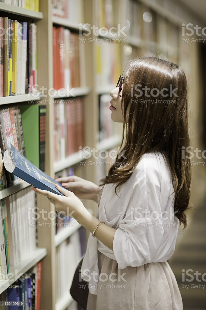 Young woman choosing books in a bookstore royalty-free stock photo