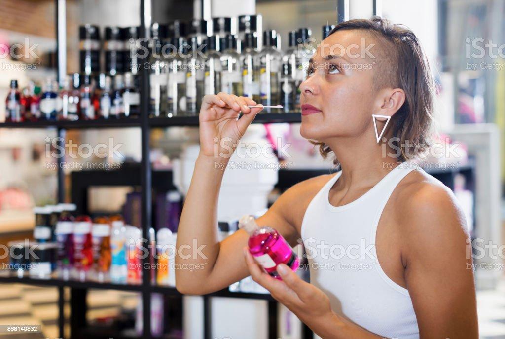 Young woman choosing bottle of pheromones in sex shop stock photo