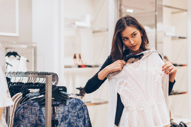 Young woman choosing clothes in the store Beautiful young woman holding a new dress in a fashion store lace textile stock pictures, royalty-free photos & images