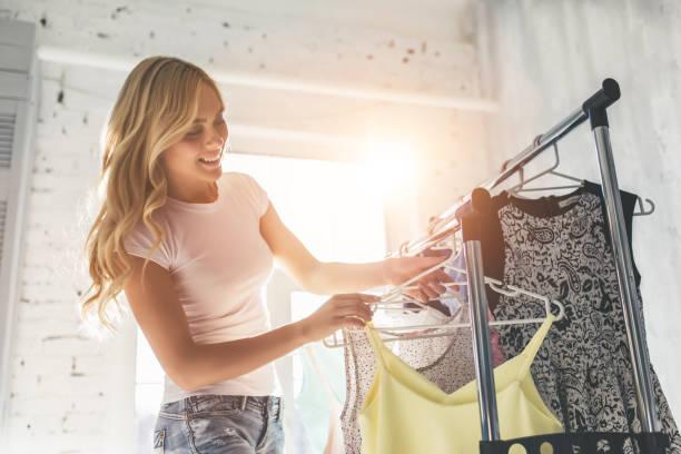jeune femme en choisissant des vêtements - vêtements photos et images de collection