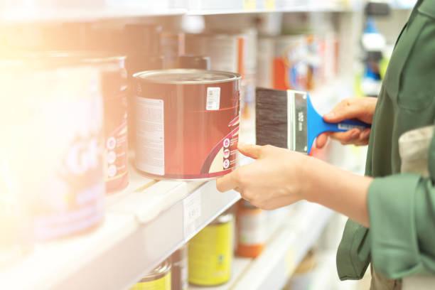 junge frau wählen farbe farbe im baumarkt. kopieren sie den speicherplatz. paint-store-shopping-konzept. - baumarkt stock-fotos und bilder
