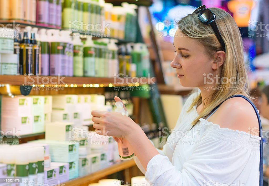 Jeune femme choisissant de crème de beauté et de maquillage. - Photo
