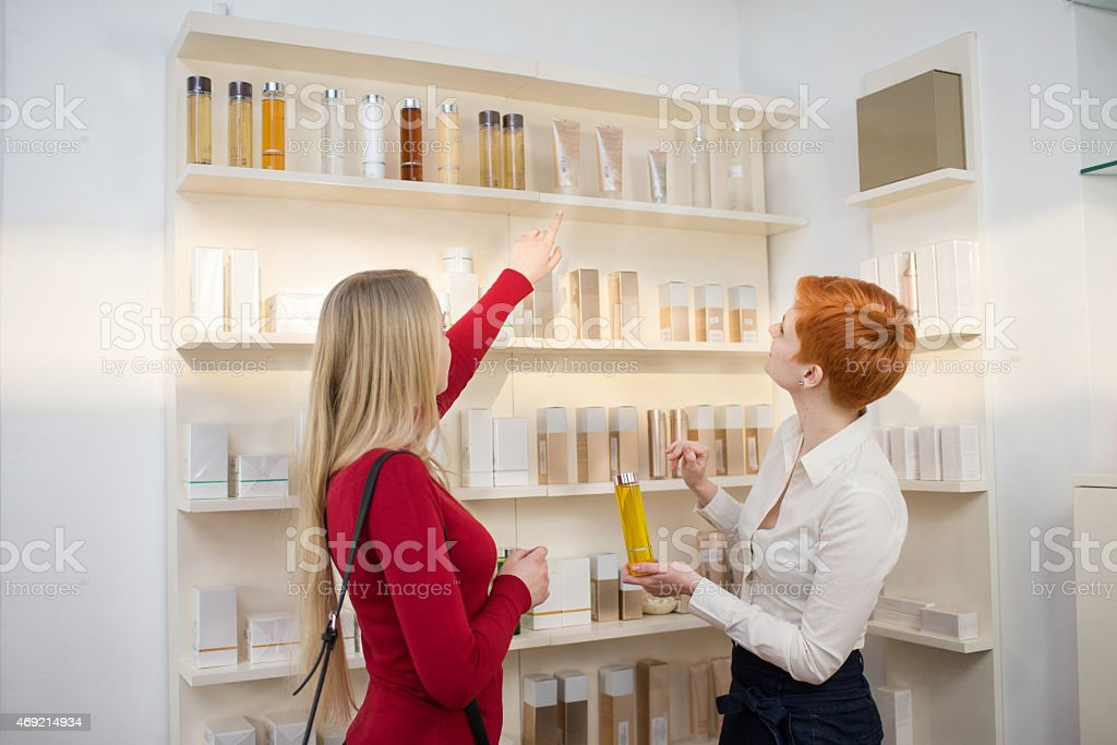 Young woman choosing cosmetics products in a drugstore stock photo