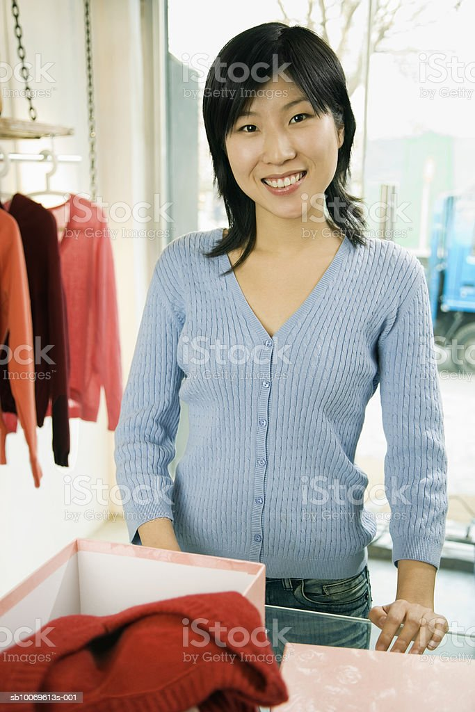 Young woman choosing dress in shop, smiling, portrait royalty free stockfoto