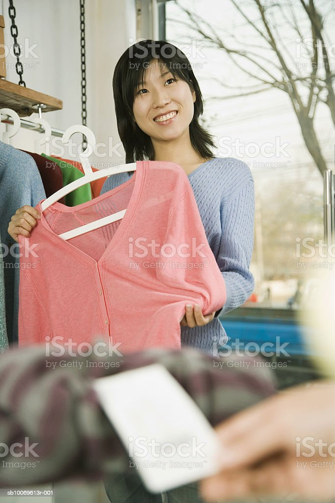 Young woman choosing dress in store, smiling photo libre de droits