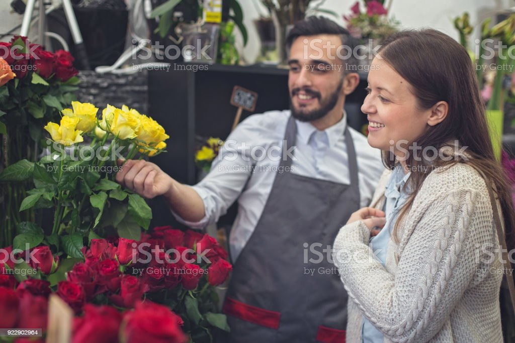 Man selling flowers to a woman in a florist shop