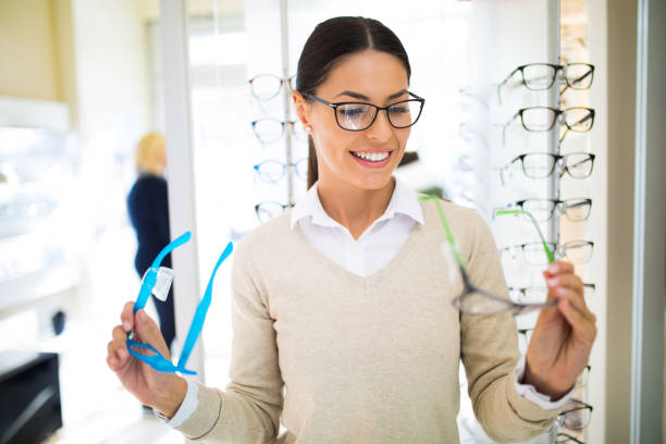 Young woman choosing glasses in optical shop stock photo