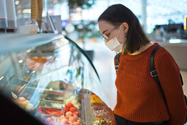 Junge Frau wählt Eis und trägt schützende medizinische Maske – Foto