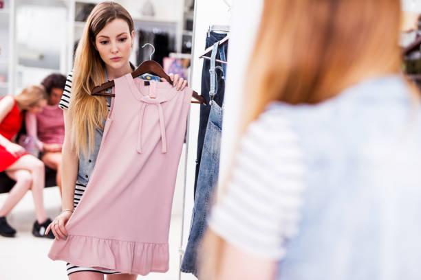 junge frau wahl neue rosa kleid in einer modeboutique - kleider günstig kaufen stock-fotos und bilder