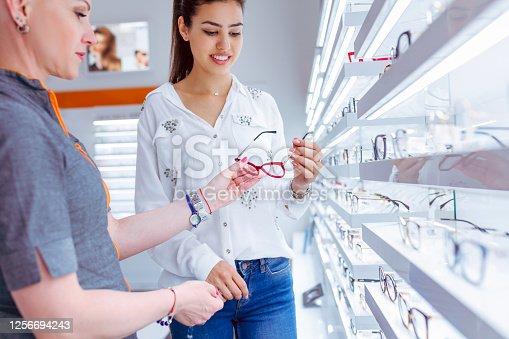 Female sales clerk helping customer to choose perfect eyeglasses, handing eyewear to customer