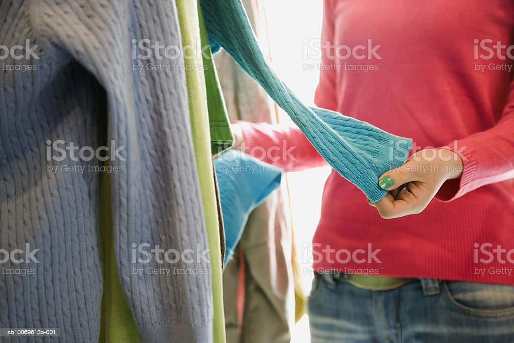 Young woman choosing sweater in shop, mid section royalty-free stock photo