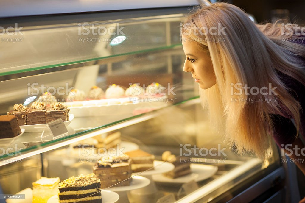 Young woman choosing sweets stock photo