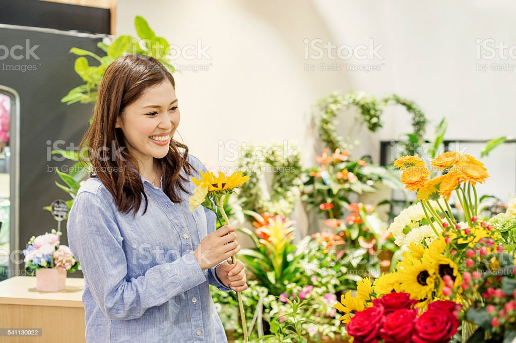 Young woman having good time in flower shop