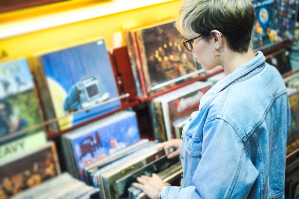 Young Woman Choosing Vintage Vinyl LP In Records Shop stock photo