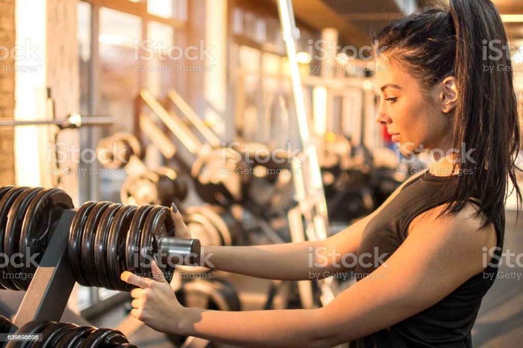 Young woman choosing weights for her workout in gym. stock photo