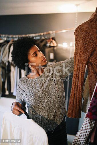 Young mixed race woman in her apartment in downtown Los Angeles is checking out her wardrobe, choosing what to wear today.